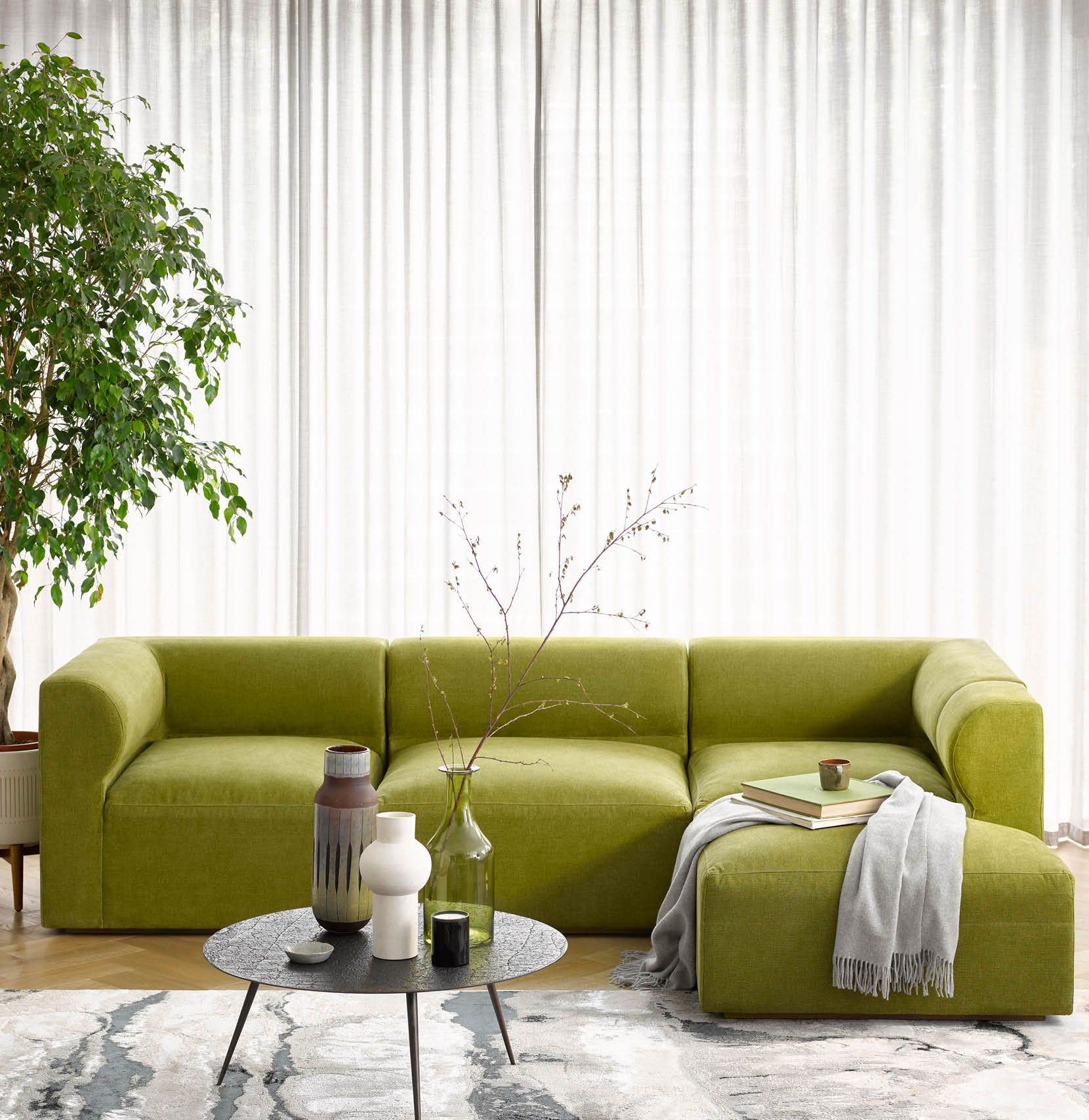 Cool cocooning - Cohen corner modular sofa in a moss green fabric, styled in a contemporary interior space